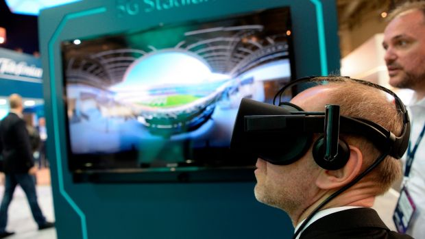 A visitor tests a virtual reality headset at the Telefonica stand at the Mobile World Congress. Photograph: Josep Lago/AFP