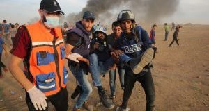 Palestinian paramedics and journalists carry a  journalist wounded by Israeli fire during a protest by Palestinians along the Gaza-Israel border in the Gaza Strip on October 5th, 2018. Photograph: Said Khatib/AFP/Getty Images