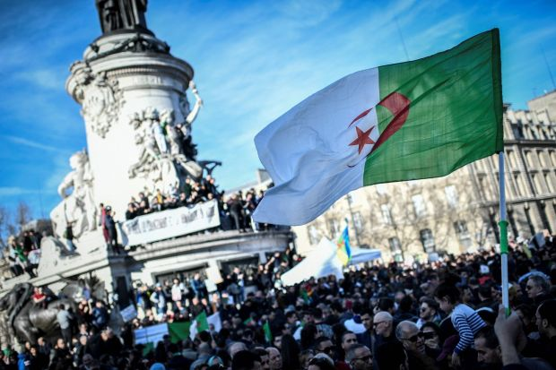 A protester holds up the Algerian flag during a rally against the Algerian president's bid for a fifth term in office at the Place de la République in Paris. Photograph: Stephane de Sakutin/AFP/Getty