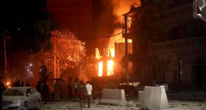 People look at flames at the scene where a suicide car bomb exploded at a hotel in Mogadishu on Thursday. Photograph: Feisal Omar/Reuters