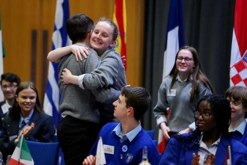 Cael Gallagher, a fifth-year student hugs Isabel Conaghan, a transition-year student, as their colleague Amanda Bates, also of transition year, looks on. The trio from St Columba's College, Stranorlar in Co Donegal were the winners of the 2019 Model Council of the European Union, representing Croatia in a discussion about how the EU should spend its budget from 2021 to 2027.  Photograph: Maxwell Photography