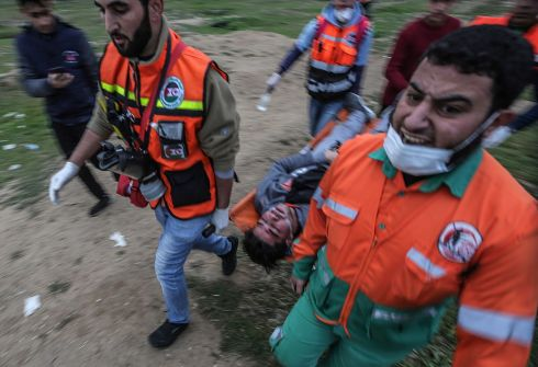 Palestinians carry a protester, wounded during clashes near the border between Israel and the Gaza Strip. Photograph: Mohammed Saber/EPA