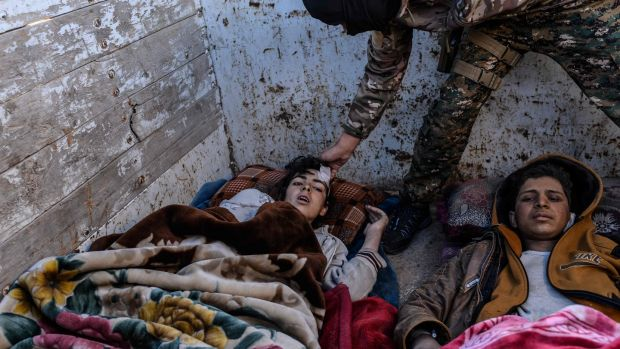 Members of the Kurdish-led Syrian Democratic Forces tend to injured boys after leaving the Islamic State (Isis) group's last holdout of Baghouz. Photograph: Getty Images