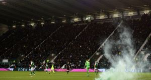 A flare on the pitch during Celtic's 2-0 win away to Hibernian. Photograph: Mark Runnacles/Getty