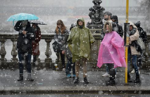 Tourists on O'Connell Bridge in Dublin city centre, as snow fell on Sunday. Photograph: Dara Mac Donaill/The Irish Times