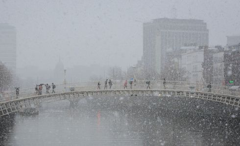 Snow swirls around the Liffey and the Ha'penny Bridge in Dublin city centre. Photograph: Gareth Chaney Collins