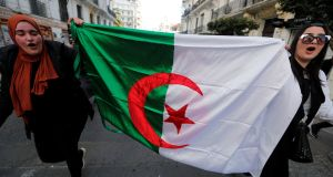 Students hold an Algerian flag as they take part in a protest in Algiers on Tuesday. Photograph: Zohra Bensemra/Reuters