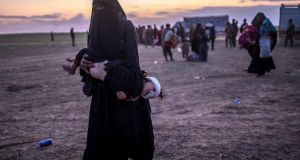 A woman carries her injured child after leaving Islamic State's last holdout of Baghouz, Syria. Photograph: Bulent Kilic/AFP/Getty Images