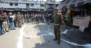 A policeman stands guard at the site of a grenade blast in Jammu, Kashmir. Photograph:Mukesh Gupta/Reuters