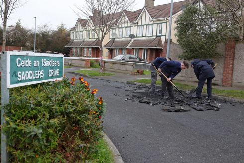 Gardaí examine the scene on Saddlers Drive in Mulhuddart, Co Dublin, where the suspected getaway car used in the shooting of Lee Boylan was discovered after it had been set alight. Picture Colin Keegan/Collins Dublin