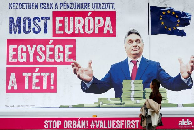 A pedestrian looks at a billboard truck showing a picture of Hungary's Viktor Orban which reads; 'First he just wanted to take our money, now the unity of Europe is at stake', outside the European Parliament in Brussels on November 6th. Photograph: Francois Lenoir/Reuters/File