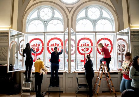 The women's sign in the Danner Foundation's house is repainted on Women's Day in Copenhagen, Denmark. This year it is 40 years since the women's characters were painted on the windows for the first time, when the house was occupied by 300 feminists.  EPA/Nils Meilvang