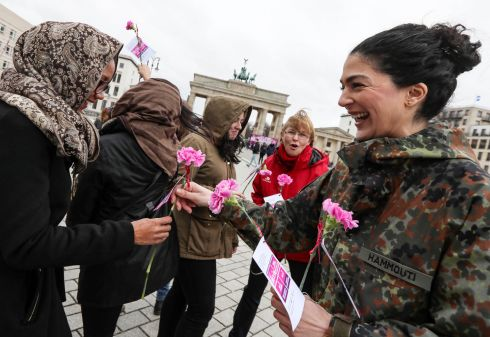 A female soldier of the German Armed Forces distributes flowers to women near the Brandenburg Gate during the International Women's Day in Berlin, Germany. Under the theme 'Think equal, build smart, innovate for change' millions of women worldwide protest for gender equality, more rights and the empowerment of women. Earlier this year the International Women's Day was declared public holiday in Berlin.  EPA/FELIPE TRUEBA