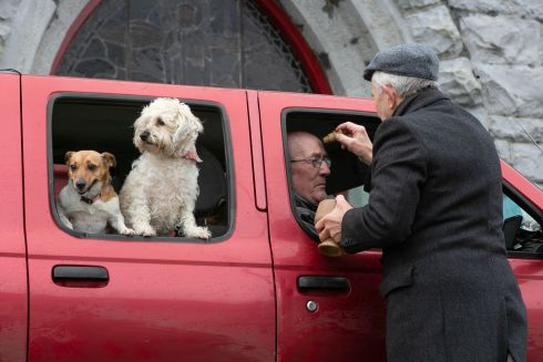 Padraig Divilly receives ashes from Fr Paddy Mooney as his dogs Penny and Misty look on at the Ash Wednesday drive-through service at St Patrick's Church in Glenamaddy, Co Galway. Photograph: Andy Newman