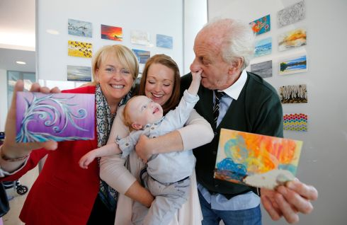 Jack & Jill CEO Carmel Doyle (left) with Joan Johnston and her 19-month-old son Leo (centre), and Irish designer Paul Costelloe (right) launch Incognito, a secret art sale in aid of the charity. Expected to be the largest fair of its kind in Ireland this year, 2,600 postcard-size original artworks will be on sale.  Photograph: Nick Bradshaw/The Irish Times