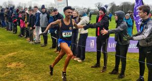 Efrem Gidey of Le Chéile Secondary School in Tyrellstown is congratulated by school-mates on his way to defending his Irish Schools Cross Country title at Clongowes Wood College in Kildare. Photograph: Ian O'Riordan