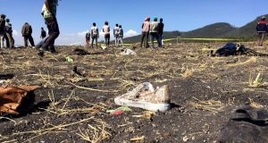 People  the crash scene with debris scattered around them. Photograph: Tiksa Negeri/Reuters