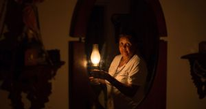 Venezuelan Elvia Helena Lozano with  a kerosene lamp  at her home in Caracas during the mass power outage. Photograph: Cristian Hernandez/AFP/Getty Images