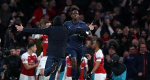A pitch invader runs towards Paul Pogba of Manchester United as he goes to join the celebration with Pierre-Emerick Aubameyang during Arsenal's 2-0 win on Sunday. Photo: Catherine Ivill/Getty Images