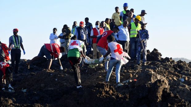 Rescue workers carry wreckage at the crash site of Ethiopia Airlines Boeing 737 Max 8. All passengers onboard the scheduled flight died. Photograph: EPA