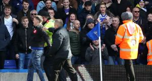 The fan who attacked Aston Villa's Jack Grealish is escorted off the pitch at St Andrew's. Photograph: PA