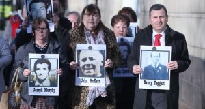 Family members hold images of some of those who died in disputed circumstance in Ballymurphy in 1971, outside Laganside Courts in Belfast as the inquest into their deaths continues. Photograph: Niall Carson/PA Wire