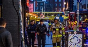 A fireman and gardaí are seen attending to a fire in the Temple Bar area of Dublin on Monday evening. Photograph: James Forde/The Irish Times.