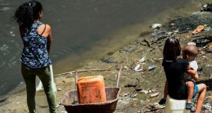 A woman collects water from a sewage canal at the river Guaire in Caracas. Photograph: Juan Barreto/AFP/Getty Images