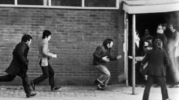 Hugh Gilmore, third left, clutching his stomach after being shot during Bloody Sunday. Photograph: PA/PA Wire