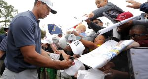 Tiger Woods signs autographs for young fans during a practice round for The Players Championship  at TPC Sawgrass  in Ponte Vedra Beach, Florida. Photograph:  Richard Heathcote/Getty Images