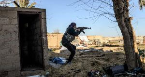 A fighter with the Syrian Democratic Forces takes aim with his Kalashnikov after seeing a man walking towards his position in Baghouz, in eastern Syria. Photograph: Bulent Kilic/AFP/Getty Images