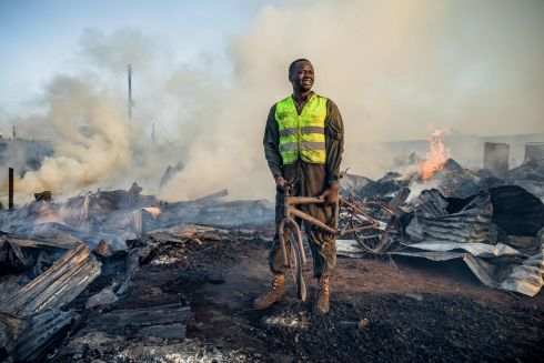 BURNT DOWN: A resident assists firefighters after a fire at Toi Market, at which second-hand clothes are closed, at Kibera slum in Nairobi, Kenya. Photograph: Brian Otieno/AFP/Getty