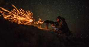 A Syrian Democratic Forces (SDF) fighter opens fire   outside the Islamic State's embattled holdout of Baghouz. Photograph: AFP/Getty Images