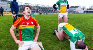 Carlow's Sean Whelan celebrates victory while Offaly's Pat Camon shows his  dejection after the Division 1B relegation play-off at O'Connor Park, Tullamore. Photograph: Tom O'Hanlon/Inpho