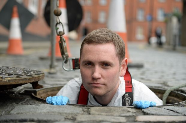 Karl Whitney, author of Hidden City: Adventures and Explorations in Dublin, at a manhole entrance to the sewerage system and to the river Poddle on Ship Street in Dublin. Photograph: Frank Miller