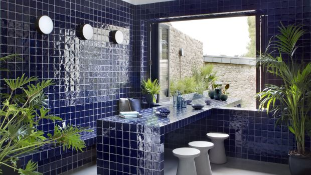 Blue tiled seating island extends outside to knit the indoor and outdoor areas into one slick space. Photograph: Barbara Corsico