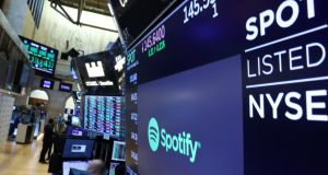 A screen displays the company logo and trading info for Spotify on the floor at the New York Stock Exchange (NYSE)