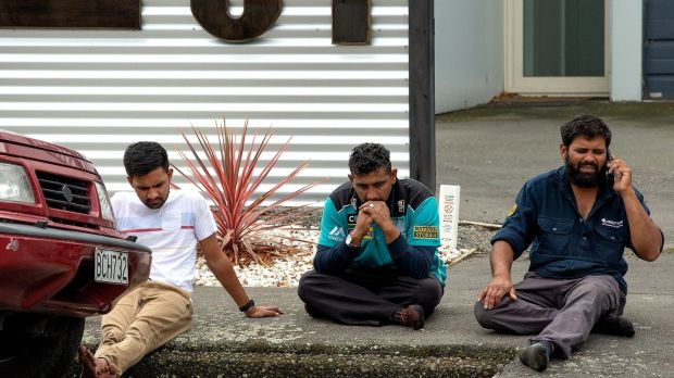 Grieving members of the public sit on a curb following a shooting at the Masjid Al-Noor mosque on Deans Avenue in Christchurch, New Zealand. Photograph: Martin Hunter/EPA