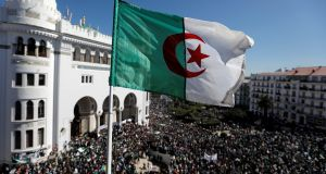 Algerian flag flutters as people protest at  President Abdelaziz Bouteflika's decision to postpone elections in Algiers, on March 15th. Photograph: Zohra Bensemra