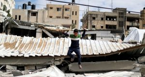 A Palestinian boy jumps at a  destroyed Hamas site following Israeli air strikes in Gaza City on March 15th. Photograph: Mohammed Salem