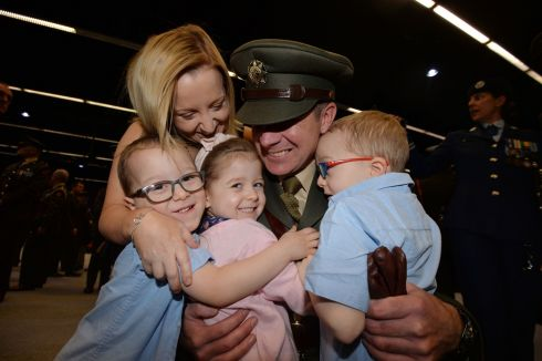 Capt John Griffin from Kilkenny being congratulated by his wife Kelly children Cian, Emma and Killian after being commissioned as an officer from the 10th Potential Officers Course at the printworks in Dublin Castle. The 10th PO Course was made up of personnel with previous experience as non-commissioned officers in the enlisted ranks of the Irish Defence Forces. Photograph: Alan Betson/The Irish Times
