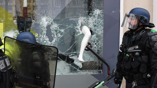 French riot police forces walk past a scooter seen in a broken store window as they clash with Yellow Vest protesters on the Champs-Élysées in Paris on Saturday. Photograph: Alain Jocard/AFP/Getty Images
