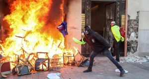 A yellow vest protester throws a European Union flag onto   a burning  barricade  at a shop on the Champs Elysees  in Paris on Saturday. Photograph: Zakaria Abdelkafi/AFP/Getty Images