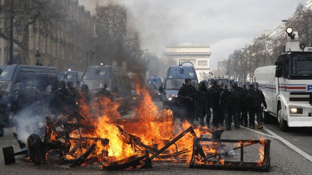 A barricade burns on the Champs Elysees in Paris. French yellow vest protesters clashed Saturday with riot police near the Arc de Triomphe as they kicked off their 18th straight weekend of demonstrations against President Emmanuel Macron. Photograph: Christophe Ena/AP Photo