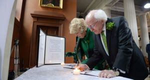 President Higgins and his wife Sabina sign a book of condolence at the Pro Cathedral for victims of the New Zealand shootings. Photograph: Dara MacDonaill