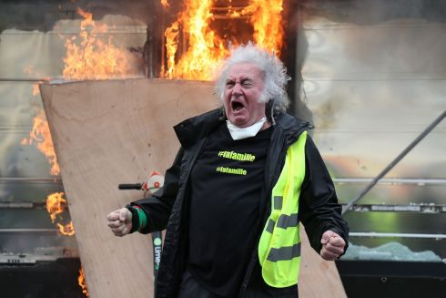 FIRED UP: A yellow vest protester gestures in front of a newsagent set on fire during clashes with riot police on the Champs-Elysees in Paris, France, during the 18th consecutive Saturday of gilets jaunes demonstrations. Photograph: Zakaria Abdelkafi/AFP/Getty Images