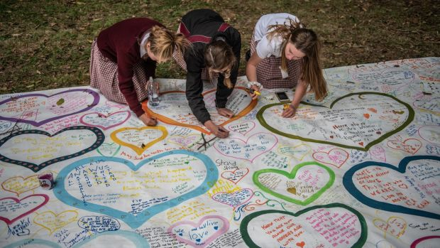 Schoolgirls write messages on a banner during a students vigil near Al Noor mosque on March 18th. Photograph: Carl Court/Getty Images