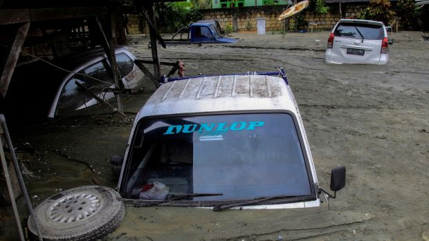 Cars are submerged in mud following a flash flood in Sentani, Papua, Indonesia. Photograph: Antara Foto/Reuters