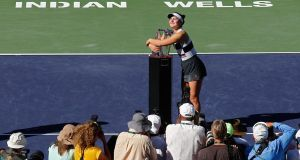 Bianca Andreescu of Canada hugs the trophy after beating Angelique Kerber  of Germany in the final of the  BNP Paribas Open  at Indian Wells in  California. Photograph: Larry W Smith/EPA