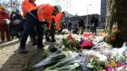 Construction workers place flowers at a makeshift memorial at the site of a tram shooting in Utrecht, on Tuesday. Photograph: Piroschka van de Wouw/Reuters